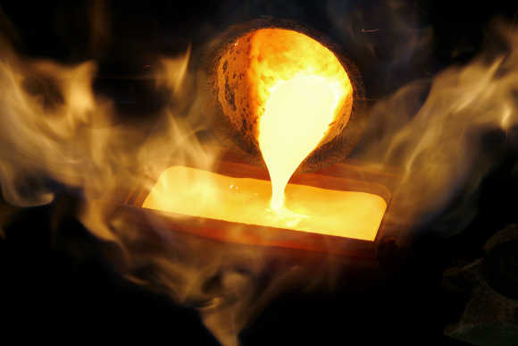 Melted gold flows out of a smelter into a mould of a one kilogramme bar at a plant in Swiss town of Mendrisio.
