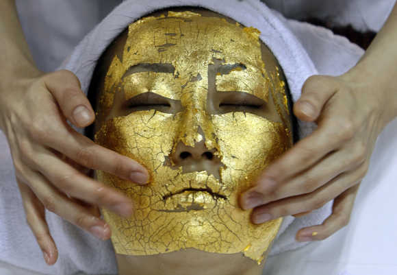 A model demonstrates the use of Umo Inc's 24-carat gold leaf 'Gold Facial Treatment' in Tokyo.