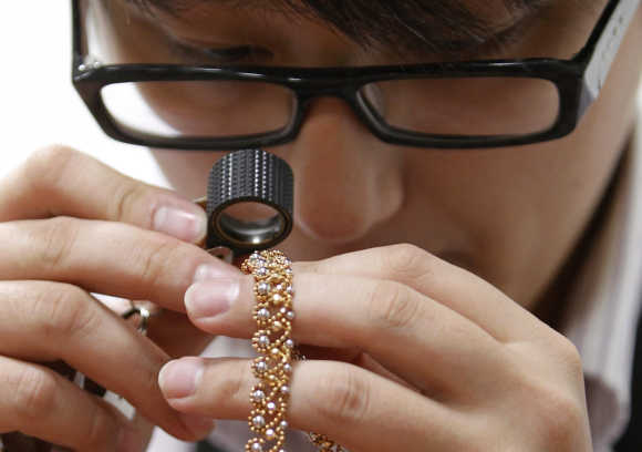 An employee inspects a piece of jewellery at a shop that purchases gold in the Ginza district of Tokyo.