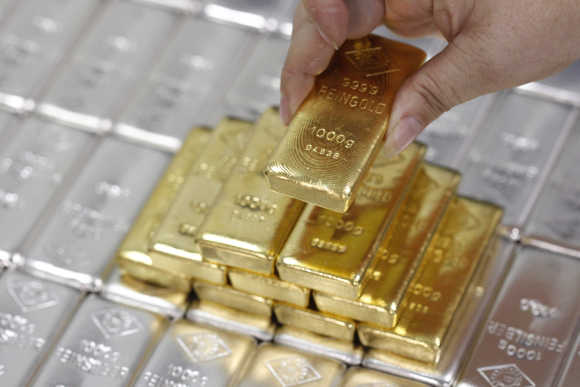An employee picks up a gold bar at the Austrian Gold and Silver Separating Plant 'Oegussa' in Vienna.