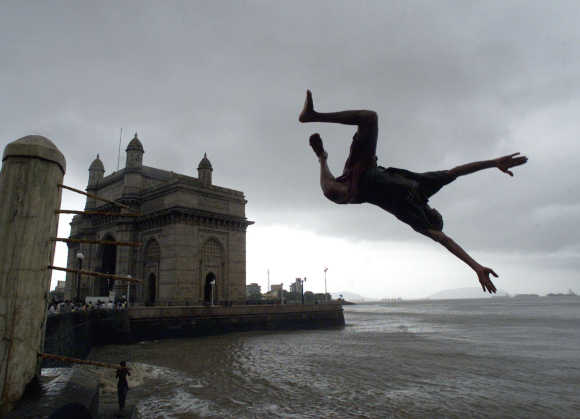 A boy jumps into the Arabaian Sea next to Gateway of India in Mumbai.