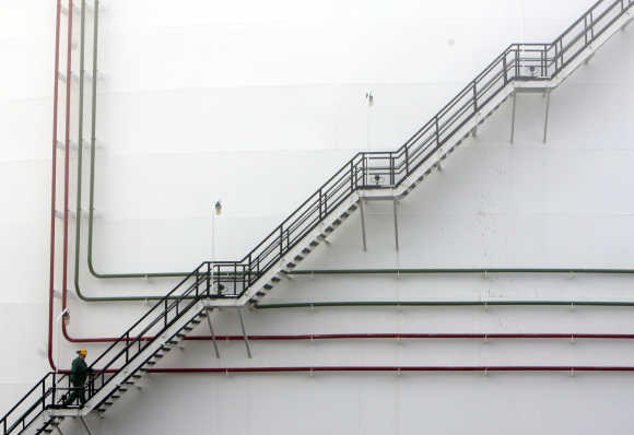 An employee walks up a flight of stairs at one of the huge tanks storing strategic oil reserves at Hungarian oil and gas group MOL's main Duna (Danube) refinery in Szazhalombatta, Hungary.