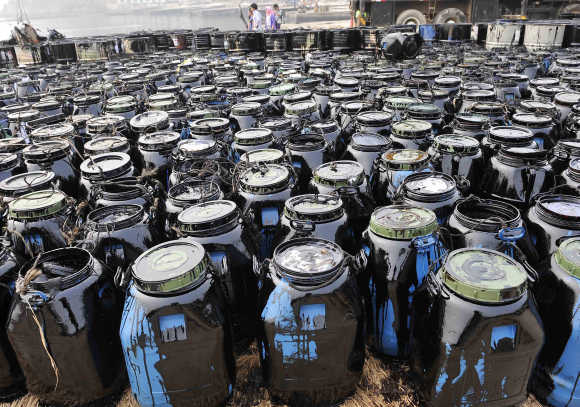 Containers filled with oil cleaned up from the oil spill site are seen at Beilianggang port in Dalian, Liaoning province, China.