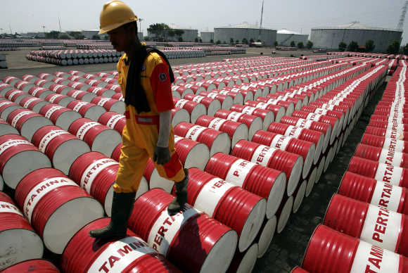 An employee of Indonesian oil company Pertamina walks on the top of drums at the oil storage depot in Jakarta.