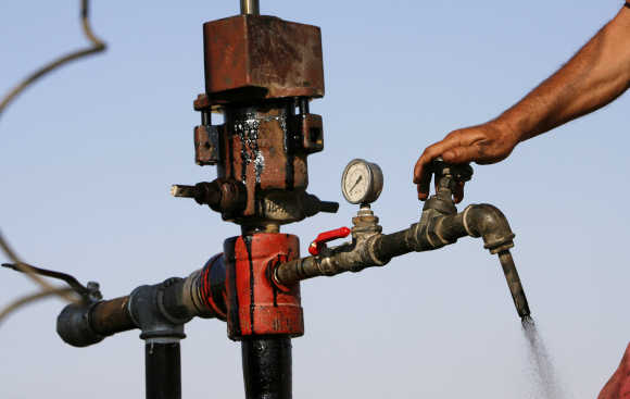 A worker turns a valve to release drilled oil, near the Dead Sea, Israel.