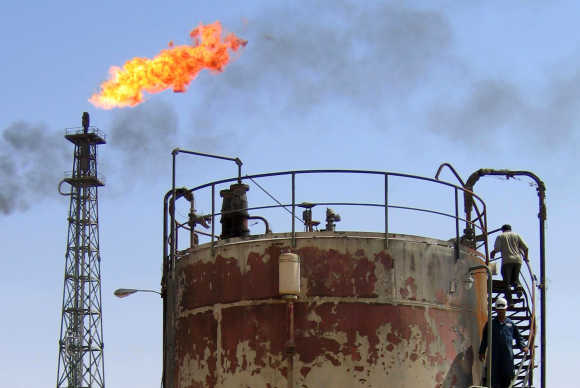 Workers check equipment at the Al-Shuaeba oil refinery, about 15km southeast of the Iraqi city of Basra.