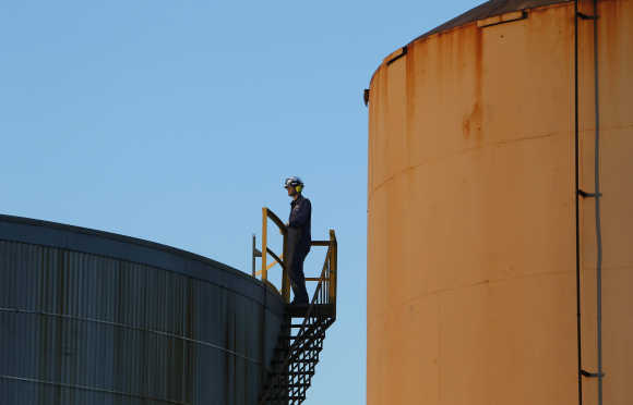 A worker is seen on top of a fuel storage tank at an oil refinery in Melbourne.
