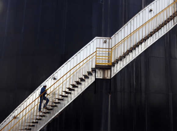 An employee of the Canadian Pacific Rubiales Petroleum Company ascends an oil storage tank in Campo Rubiales field in Meta, eastern Colombia.