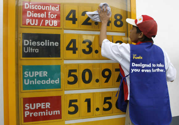 A worker wipes the price display board at a petrol station in Manila.