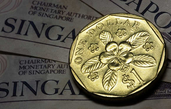 A Singapore one dollar coin rests on top of Singapore two dollar notes.
