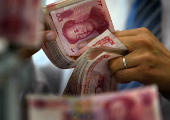 An employee counts yuan notes at a bank in Nanjing.