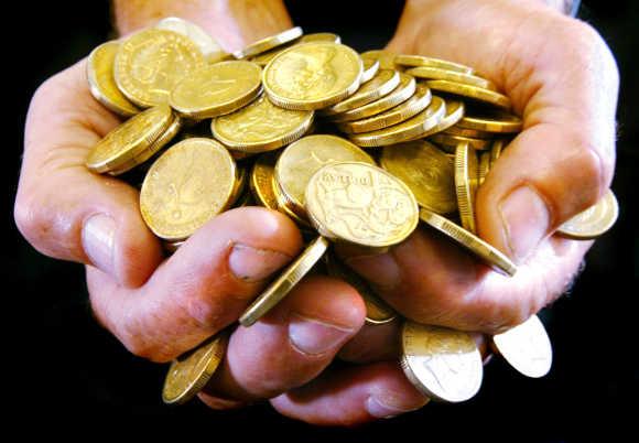 A handful of Australian one dollar coins in Sydney.