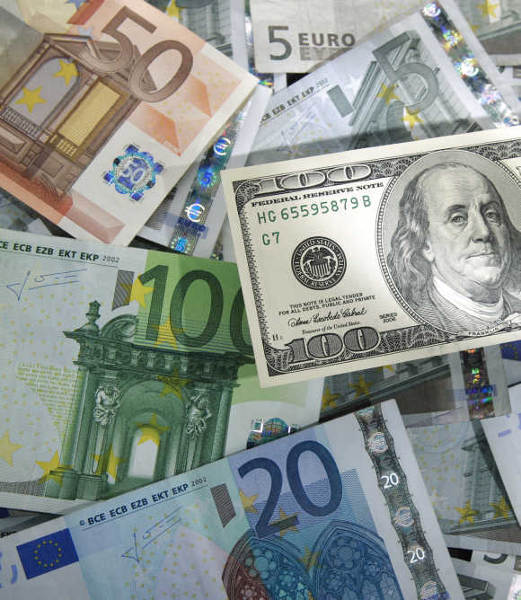 A picture illustration shows a $100 banknote on various denomination of euro banknotes in Warsaw.