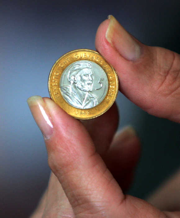 Cuban woman holding new convertible five peso coin bearing the face of Che Guevara.