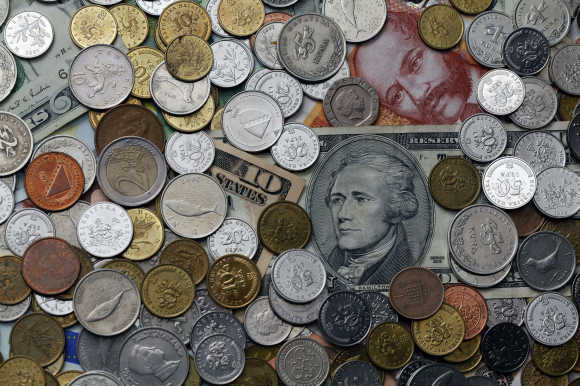 A picture illustration of coins from various countries laying on kuna and dollar banknotes in Zagreb, Croatia.