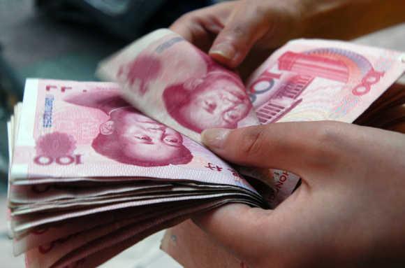 Shop assistant checks hundred yuan bank notes at shop in Xiangfan, China.