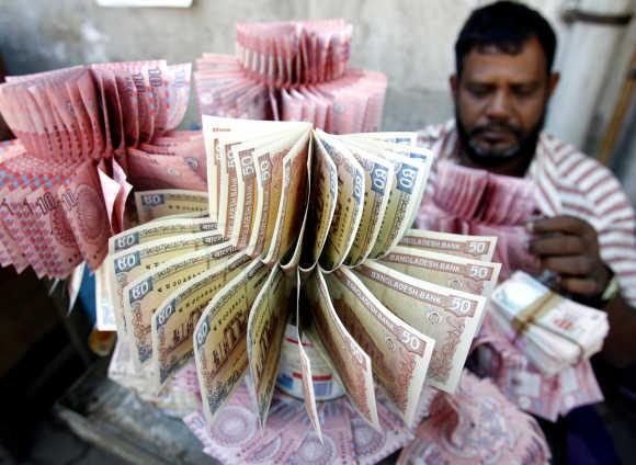 Money vendor displays crisp Bangladeshi takas of different denominations in Dhaka.