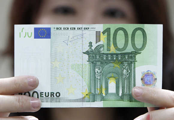 An employee checks a euro note at the Bank of Taiwan in Taipei.