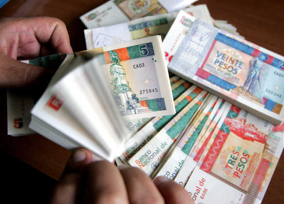 A man counts freshly printed Cuban convertible peso notes in Havana.