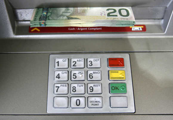 A bank machine dispenses Canadian dollars in Toronto.