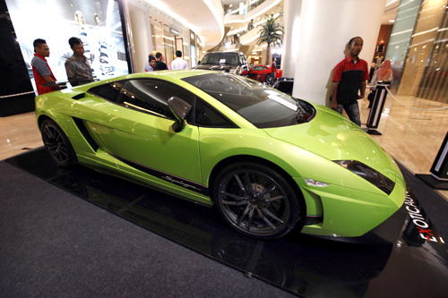 Men look at a Lamborghini on display at a shopping mall in Jakarta.
