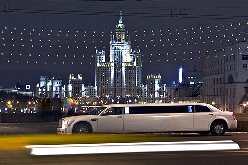 Cars drive past sightseers on a bridge over the Moskva river near a Stalin era skyscraper in central Moscow.