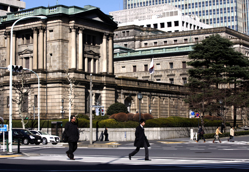 Pedestrians cross a street in front of the Bank of Japan (BOJ) headquarters building in Tokyo.