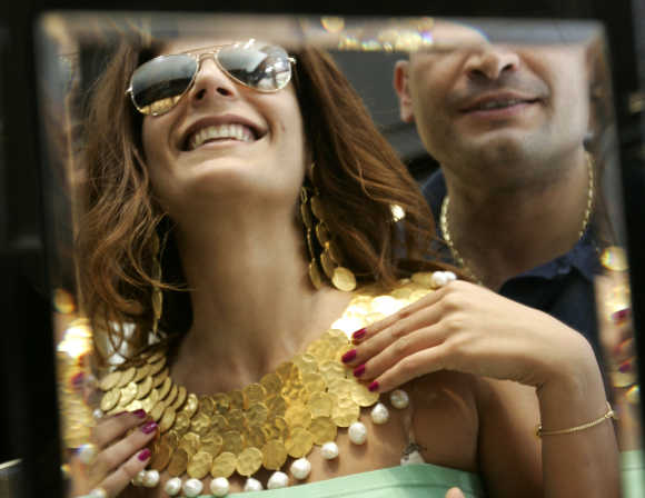 A salesman helps a customer to try on a jewellery set at a shop in a shopping district in Beirut