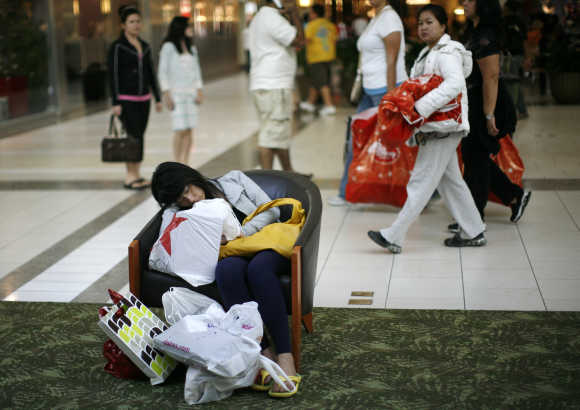 A woman sleeps after shopping during 'Black Friday' sales at the Dadeland Mall in Miami.