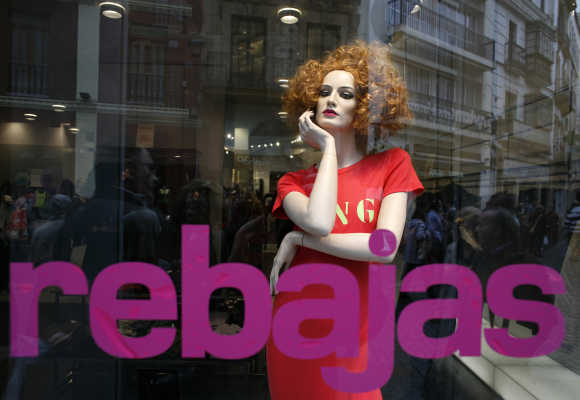 People are reflected on a shop window in Seville, Spain.