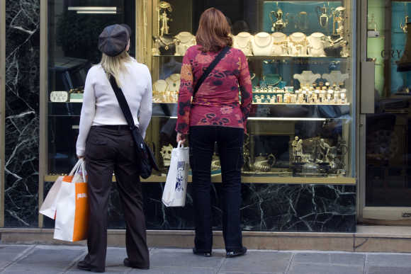 Women carry shopping bags as they look at a window display of a jewellery shop in central Paris.