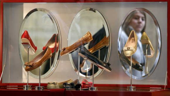 A shopper is reflected in a shoe shop window in downtown Rome.