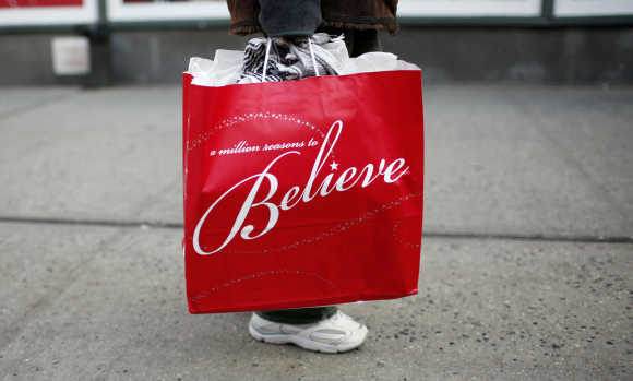 A woman carries a shopping bag from Macy's department store as she walks along 34th street in New York City.