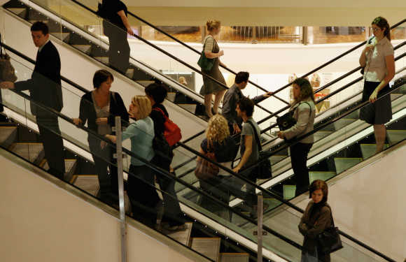 Customers use the escalators at a shopping centre.