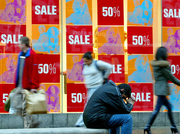 Shoppers pass sales signs in shop windows in Oxford Street, London.