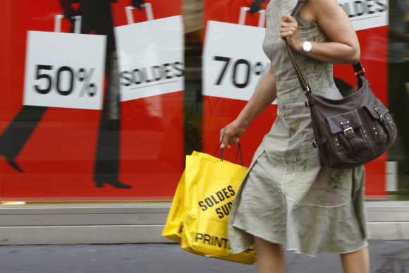 A woman walks by a shop with discount signs announcing summer sales in Paris.