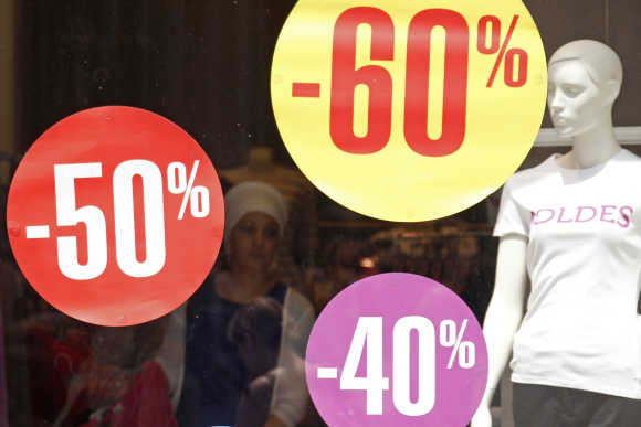 Discount signs are displayed in a clothing store window in Strasbourg, France.