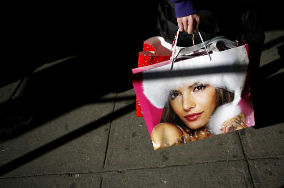 A shopper holds her purchases as she walks down the street at Herald Square in New York.