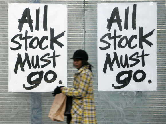 A woman passes a sign saying 'All Stock Must Go' in Croydon, London.