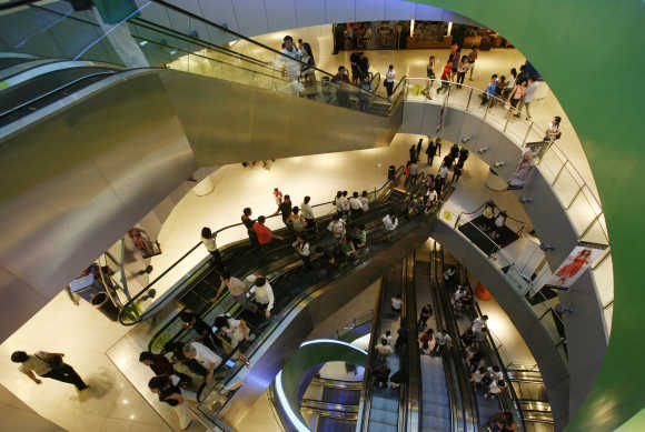 Shoppers use escalators inside a shopping mall.