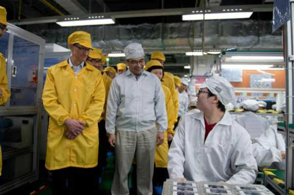 Apple CEO Tim Cook, left, visits the iPhone production line at the Foxconn Zhengzhou Technology Park in Zhengzhou, Henan province, China.