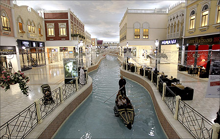 A family takes a sampan ride on a canal inside Villagio Mall, a popular shopping area in Doha.