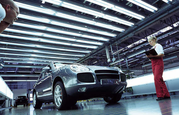 Workers perform a quality check on a Cayenne car at the Porsche factory in Leipzig, Germany.