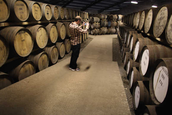 A tourist takes a photograph at Edradour distillery.