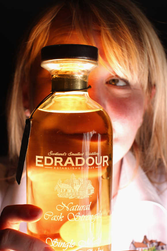 Julie Cameron, tour guide, holds a bottle of whisky at Edradour distillery.