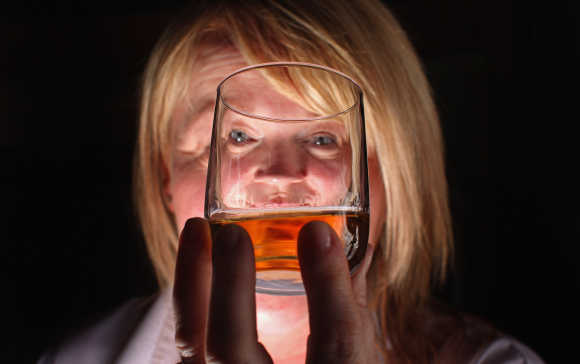 Julie Cameron, tour guide, holds a glass of whisky at Edradour distillery.