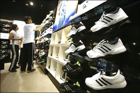 Staff arrange shoes at Adidas Brand Center store in Beijing.