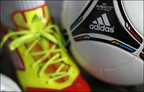 A shoe and a soccer ball by German sporting goods maker are pictured before the company