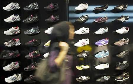 An Iranian woman walks past a window of an Adidas store in northern Tehran.