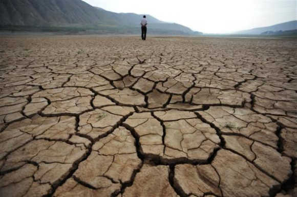 A local resident walks on a dried-up riverbed at Huangyangchuan reservoir in Lanzhou, Gansu province, China.